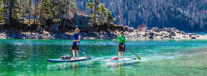 A Couple of paddle boarders on a mountain lake